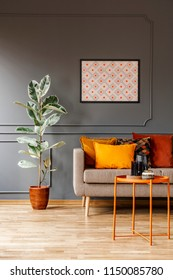 Real photo of poster with geometric pattern hanging on the wall with wainscoting in dark living room interior with fresh plant, sofa with cushions and metal end table with decorations