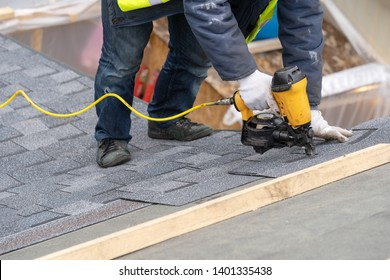 Real photo of professional roofer worker in uniform work wear using air or pneumatic nail gun and installing asphalt or bitumen shingle on top of the new roof under construction residential building