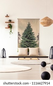 Real photo of round rugs and black balls on the wooden floor of a japanese design living room interior with white cushions on a tatami mat against the wall with tree graphic