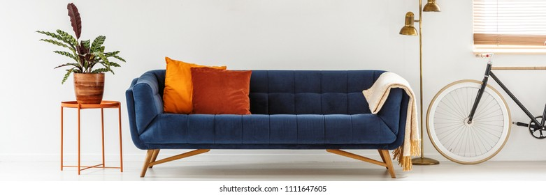 Real photo of a simple living room interior with orange cushions on a navy blue sofa standing between a metal table and golden lamp