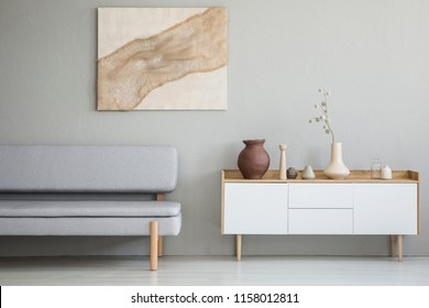 Real photo of a simple living room interior with a natural painting on the wall and gray sofa next to a wooden cupboard