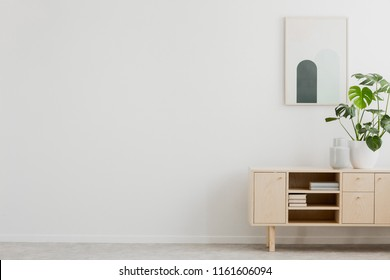 Real photo of simple poster hanging on wall, wooden cupboard with books and fresh plant and empty space for your armchair and lamp