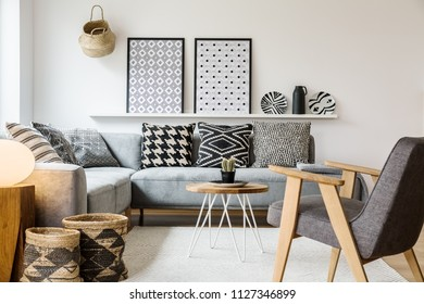 Real photo of a small table standing between a sofa with pillows and an armchair on a white rug in boho living room interior with posters on a shelf
