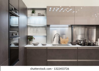 Real photo of stylish kitchen interior with glossy facade, wooden elements and built in appliances