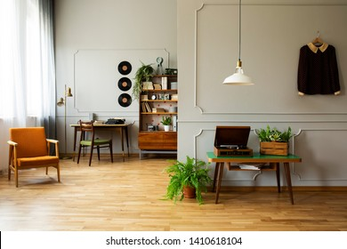 Real photo of vintage living room with orange retro armchair, desk with chair, shelf full of books and accessories and table with old gramophone