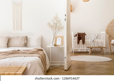 Real photo of white bedroom interior with bedside table with plant, poster and mug and open door to baby room with rug and white crib