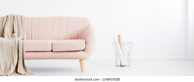 Real photo of white living room interior with metal basket with paper rolls and pastel pink couch with coverlet. Place for your armchair