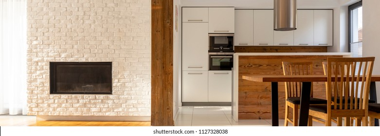 Real photo of white open space kitchen interior with two ovens, wooden countertop and dining table with chairs. Empty place on the wall above fireplace for your TV