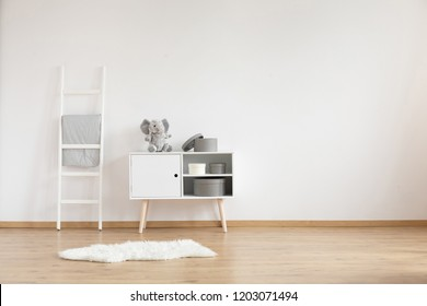 Real photo of white room interior for child with fluffy rug, ladder with coverlet and cupboard with elephant and boxes. Empty place for your crib