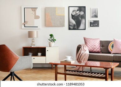 Real photo of white sitting room interior with poster on wall, couch with cushions and blanket, wooden coffee table with book and cup and plant on cupboard