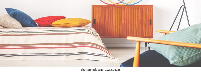 Real photo of wooden retro cupboard placed next to bed with striped coverlet and white, blue, carmine and ochre cushions in teenager room interior