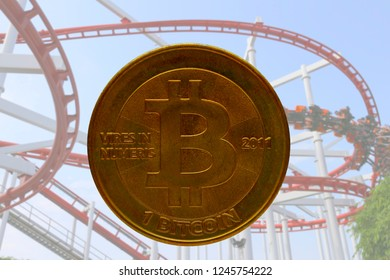real physical bitcoin with roller coaster in background to illustrate the up and down nature and volatility of crypto currencies