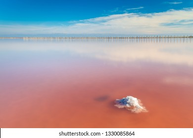 Real pink color salt lake with salt stone and deep blue sky, minimalist landscape, Ukraine, Europe