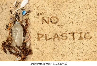 Real plastic bottle, with cap and plastic straw washed up on beach mixed with seaweed shells and feathers. Say no to plastic text