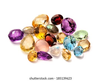 Real polished gemstones  isolated on white background. Collection of different gems: red garnet, rose and lemon quartz, brazilian amethyst, citrine, blue topaz, moonstone rainbow and labradorite.