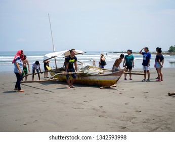 Real, Quezon, Philippines - March 12, 2019: Filipino fishermen helping each other to carry a small fishing boat to the shore in Real, Quezon, Philippines.