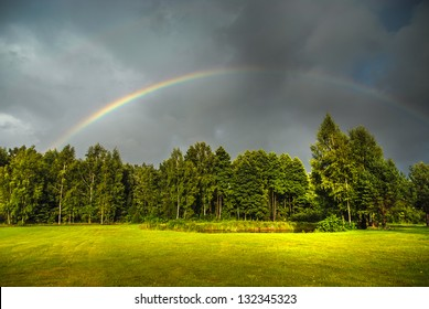 Real rainbow against a stormy sky in beautiful green countryside in summer