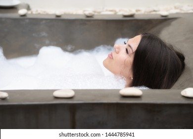 A real relax for a modern girl. Beautiful brunette takes a bath with foam.
