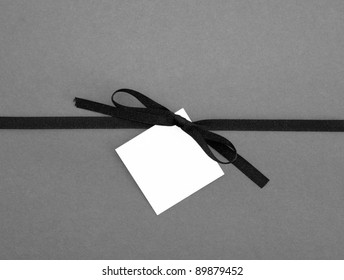 Real Ribbon Bow with Blank Note card Tag on Plain Gray Background