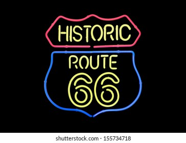 Real 'Route 66' neon sign on black background.
