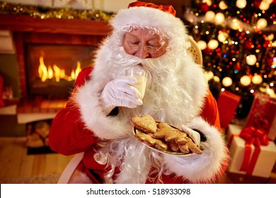 Real Santa Claus enjoying in served gingerbread cake and milk