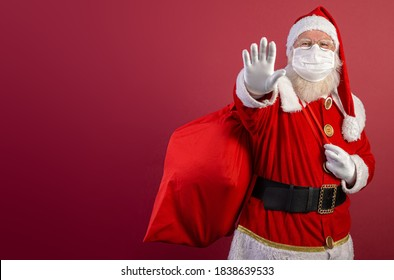 Real Santa Claus on red background, wearing protective mask and with an open hand in front making a pandemic stop sign. Christmas with social distance. Covid-19