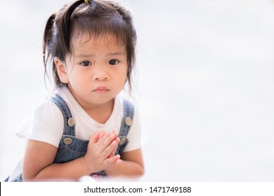 Real shot of regretful kid looks gloomy and desperate. Keeps palms together. She clasped both hands to begging for forgiveness. Feel sorry and guilty. Asian child girl adorable pleads about something.