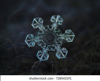Real snowflake at high magnification. Macro photo of large star plate snow crystal with short, broad arms and unusual pattern inside central hexagon. Snowflake glowing on dark gray textured background