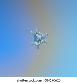 Real snowflake macro photo: small triangular snow crystal with six simple, straight arms and volume central triangle with pattern of straight lines and ridges. Snowflake glittering on blue background.