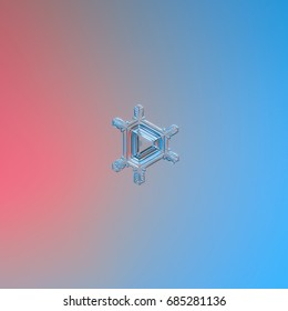 Real snowflake macro photo: small triangular snow crystal with six narrow arms, and glossy pattern of lines and ridges inside central triangle. Snowflake glittering on pink - blue gradient background.