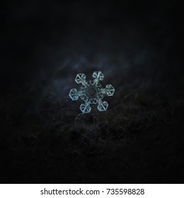 Real snowflake macro photo: star plate snow crystal with fine hexagonal symmetry, six short, broad arms and large central hexagon with unusual pattern. Snowflake glowing on dark gray background.