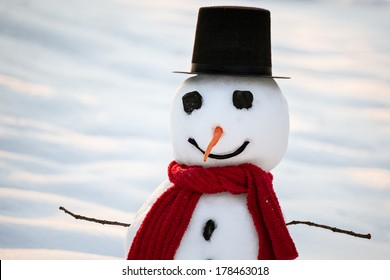 Real snowman in winter snow wearing top hat and scarf