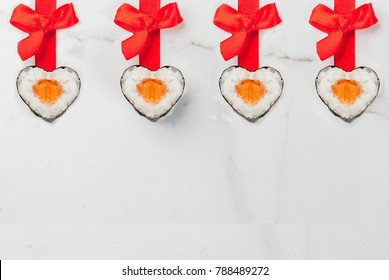 Real sushi set for valentine's day in form of hearts, with red ribbon and bow. White marble background copy space top view
