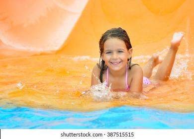 Real toddler girl enjoying her summer vacation on water slide at aquapark