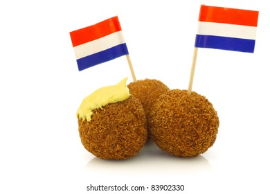 "A real traditional Dutch snack called ""bitterballen"" with mustard and  a Dutch flag toothpick on a white background"