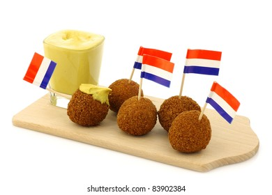 "A real traditional Dutch snack called ""bitterballen"" with a Dutch flag toothpick on a wooden cutting board on a white background"