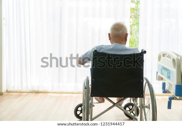 Real view of asian senior man sitting on wheelchair in rehabilitation center. Old man thinking something. Alzheimer's disease man in his wheelchair looking outside. Hope, lonely, insurance concept.
