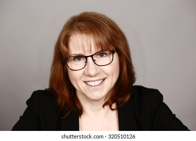 real woman business executive with glasses smiling