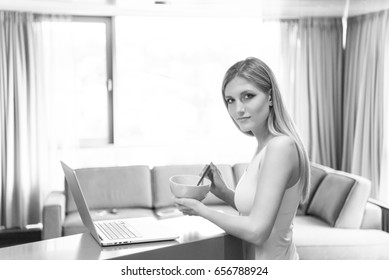 Real Woman Using laptop At Home eating breakfast Enjoying Relaxing