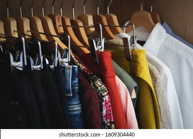 Real women's capsule wardrobe - interior of closet with clothes arranged neatly on hangers - decluttering concept