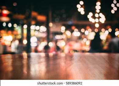 Real wood table with light reflection on scene at restaurant, pub or bar at night. Blurred background for product display or montage your products with several concept idea and any occasion.