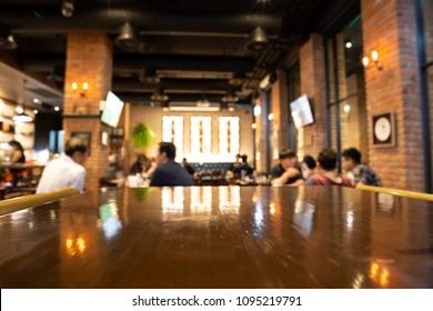 Real wood table and people with light reflection on scene at restaurant, pub or bar at night. Blurred background for product display or montage your products with several concept idea.