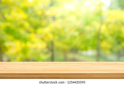 Real wood table top texture on leaf tree garden background.For create product display or design key visual layout