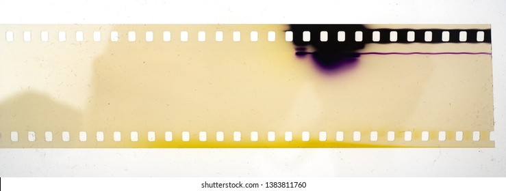 real yellow film strip with discoloration on white background