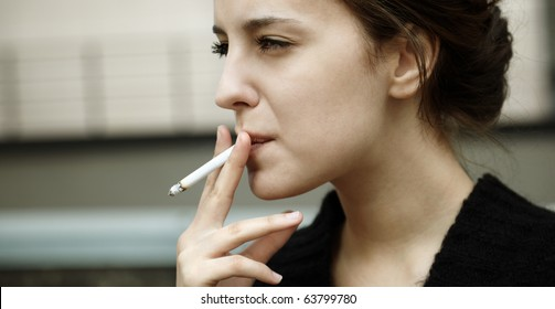 real young woman smokes on the street, selective focus