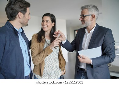 Real-estate agent handing over keys to new home owners in contemporary house