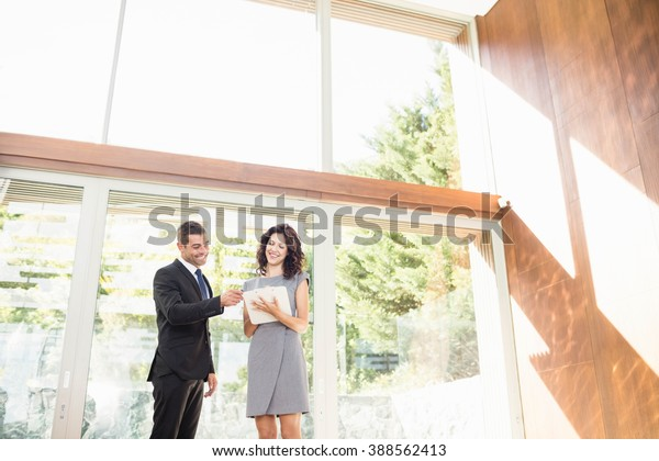 Real-estate agent interacting with young woman showing new home
