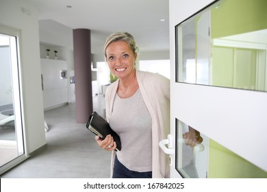 Real-estate agent presenting modern house