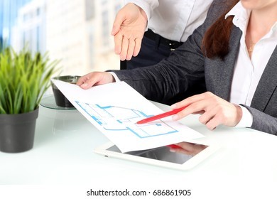 Real-estate agent showing house plans to a businessman. Focus on a hand