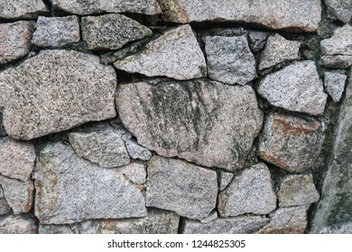 Realistic big stone made for wall with rustic & grunge texture background. Closeup of Rock wall built with natural flagstones & wall-stones of irregular shapes & sizes. Wall Detailed with copy space